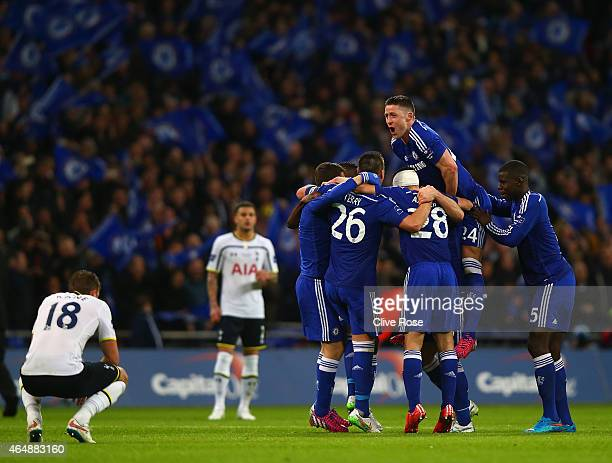 A dejected Harry Kane of Spurs looks on as Gary Cahill of Chelsea jumps on team mates as they celebrate winning the Capital One Cup Final match...