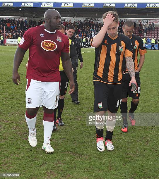 A dejected Jake Hyde of Barnet leaves the pitch at the end of the match as Adebayo Akinfenwa of Northampton Town looks on after defeat ensured...