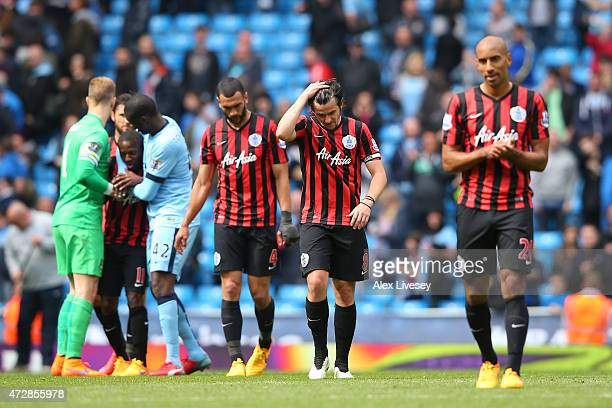 A dejected Joey Barton of QPR and teammates react following their team's relegation during the Barclays Premier League match between Manchester City...