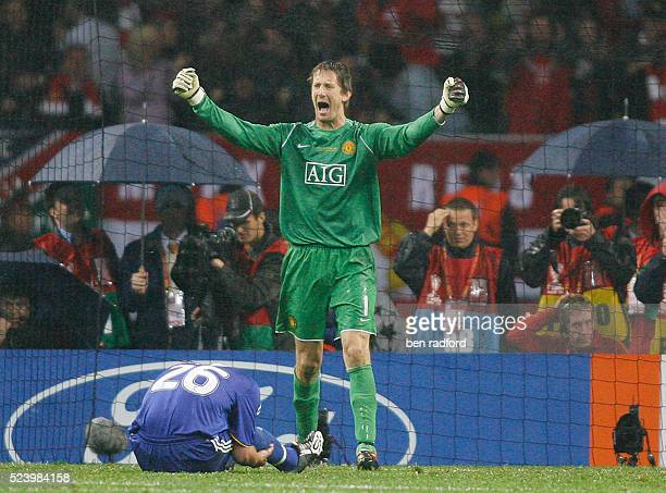 A dejected John Terry of Chelsea sits on the ground after missing his penalty as goalkeeper Edwin Van Der Sar of Manchester United celebrates during...