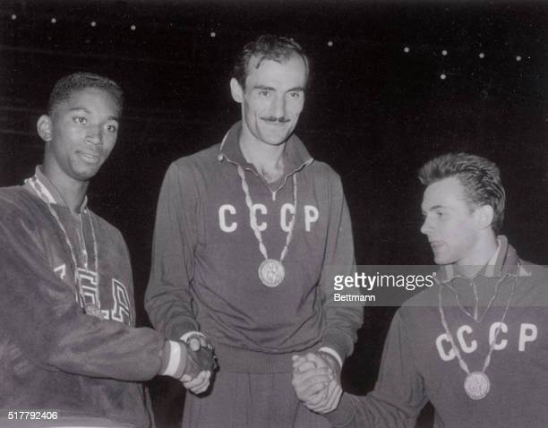 A dejected John Thomas of the United States is shown with Russia's Robert Shavlakadze and Valery Brumel after both Russians finished ahead of him in...