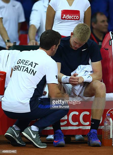 A dejected Kyle Edmund of Great Britain receives instructions from Leon Smith the Captain of Great Britain during the singles match against David...