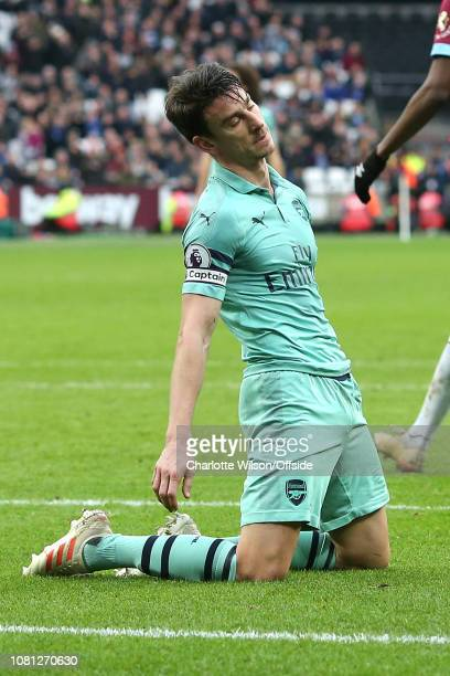 Dejected Laurent Koscielny of Arsenal falls to his knees during the Premier League match between West Ham United and Arsenal FC at London Stadium on...