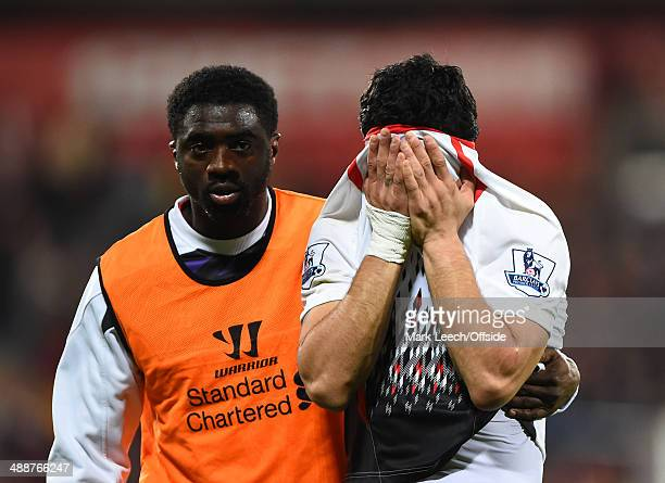 A dejected Luis Suarez of Liverpool covers his face as he leaves the pitch with Kolo Toure with his title aspirations in tatters during the Barclays...