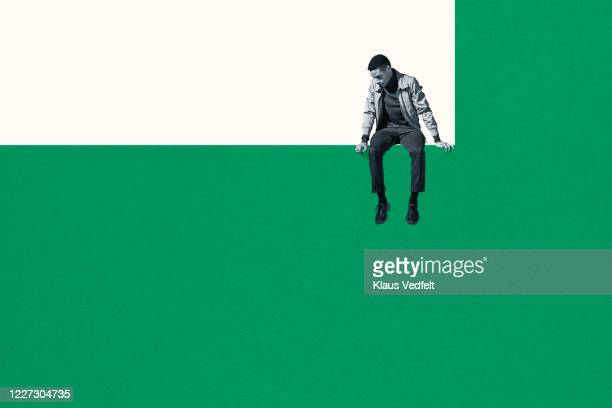 dejected man sitting on wall while looking down - ツートンカラー ストックフォトと画像