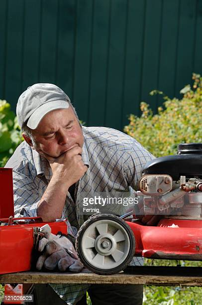 Dejected man trying to fix a broken lawnmower