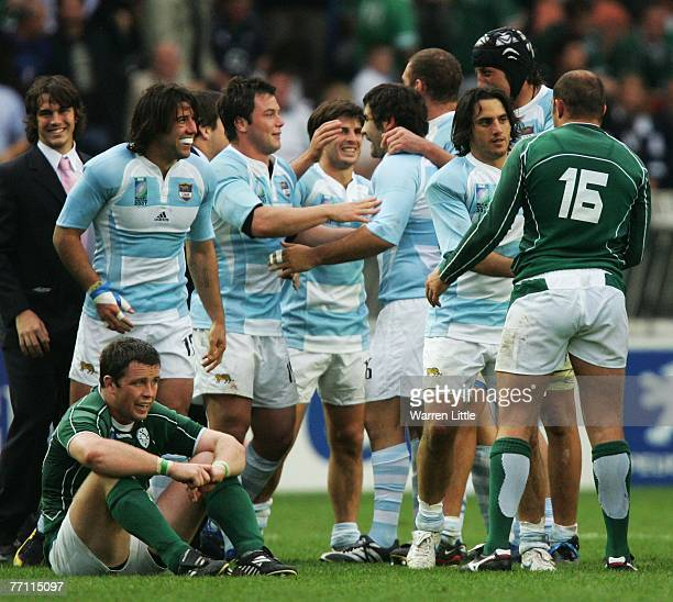 A dejected Marcus Horan of Ireland sits on the pitch as the Argentina players celebrate their 3015 victory during the Rugby World Cup 2007 Pool D...
