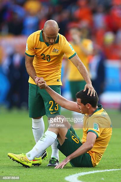 Dejected Mark Bresciano and Ryan McGowan of Australia react after being defeated by the Netherlands 3-2 during the 2014 FIFA World Cup Brazil Group B...