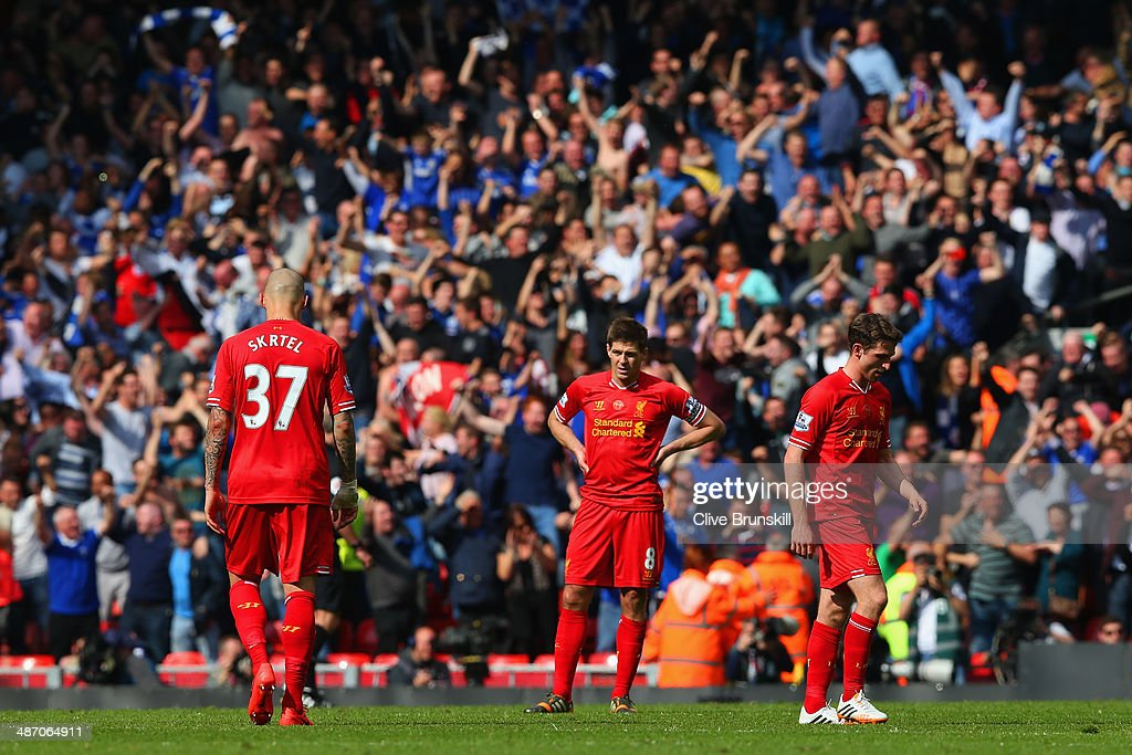 A dejected Martin Skrtel, Steven Gerrard and Joe Allen of Liverpool look on as the Chelsea fans celebrate after Willian of Chelsea scored their second goal during the Barclays Premier League match between Liverpool and Chelsea at Anfield on April 27, 2014 in Liverpool, England.
