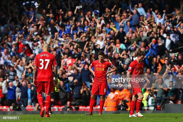 A dejected Martin Skrtel Steven Gerrard and Joe Allen of Liverpool look on as the Chelsea fans celebrate after Willian of Chelsea scored their second...