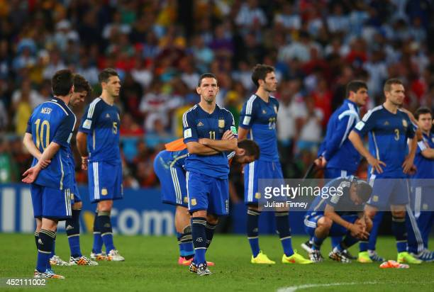 A dejected Maxi Rodriguez of Argentina looks on with teammates after being defeated by Germany 10 in extra time during the 2014 FIFA World Cup Brazil...