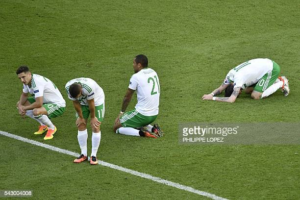 Dejected Northern Ireland players rest on the pitch after loosing 0-1 in a own goal during the Euro 2016 round of sixteen football match Wales vs...