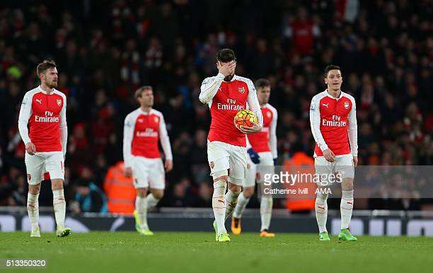 A dejected Olivier Giroud of Arsenal walks back with his team after Swansea City score to make it 12 during the Barclays Premier League match between...