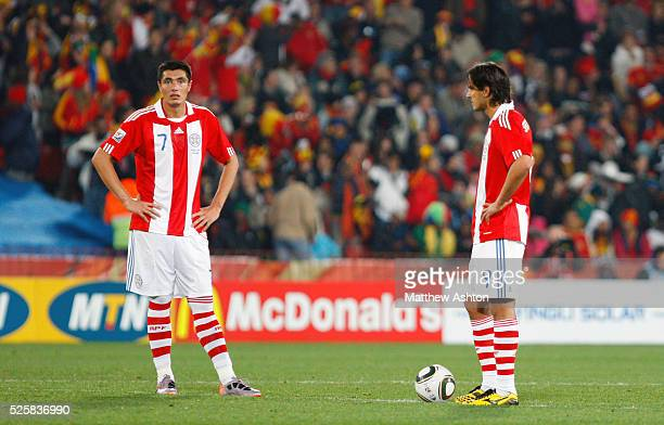 A dejected Oscar Cardozo and Roque Santa Cruz of Paraguay stand at the centre spot after David Villa of Spain scores a goal to make it 01