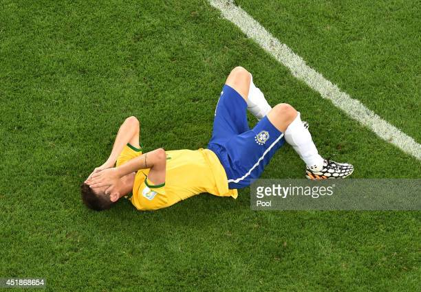 Dejected Oscar of Brazil lies on the pitch after being defeated by Germany 7-1 during the 2014 FIFA World Cup Brazil Semi Final match between Brazil...