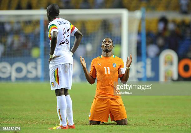 A dejected Ousmane Coulibaly of Mali as Didier Drogba of Ivory Coast preys and gives thanks after the 2012 African Cup of Nations SemiFinal match...
