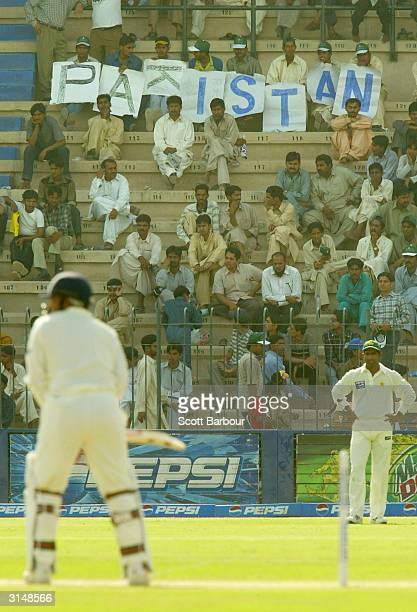 Dejected Pakistan fans look on as Virender Sehwag of India bats during day one of the 1st Test Match between Pakistan and India at Multan Stadium on...