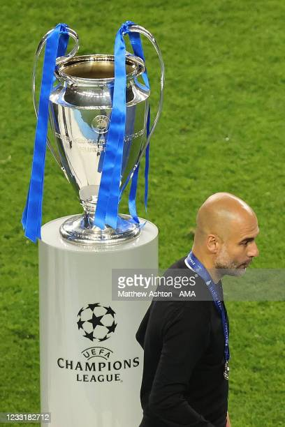 Dejected Pep Guardiola the manager / head coach of Manchester City walks past the UEFA Champions League trophy in defeat during the UEFA Champions...