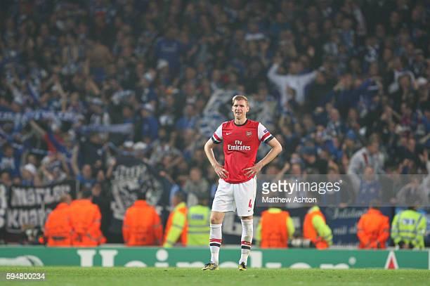 A dejected Per Mertesacker of Arsenal stands infront of the Schalke fans