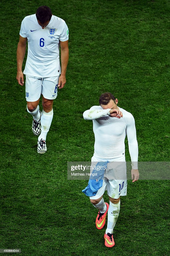 A dejected Phil Jagielka (L) and Wayne Rooney of England walk off after being defeated by Uruguay 2-1 during the 2014 FIFA World Cup Brazil Group D match between Uruguay and England at Arena de Sao Paulo on June 19, 2014 in Sao Paulo, Brazil.