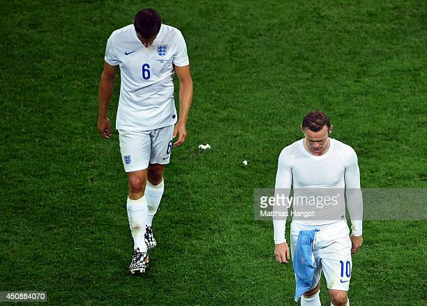 A dejected Phil Jagielka and Wayne Rooney of England walk off after being defeated by Uruguay 21 during the 2014 FIFA World Cup Brazil Group D match...