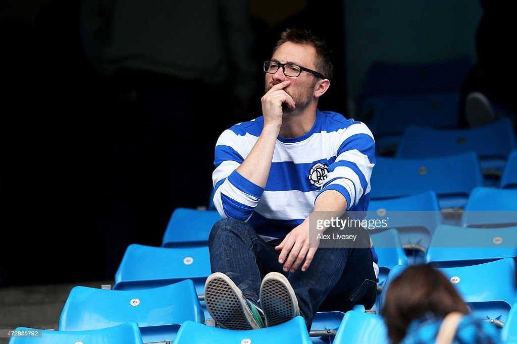 Dejected QPR fan reacts as his team is relegated following the final whistle during the Barclays Premier League match between Manchester City and Queens Park Rangers at the Etihad Stadium on May 10, 2015 in Manchester, England.