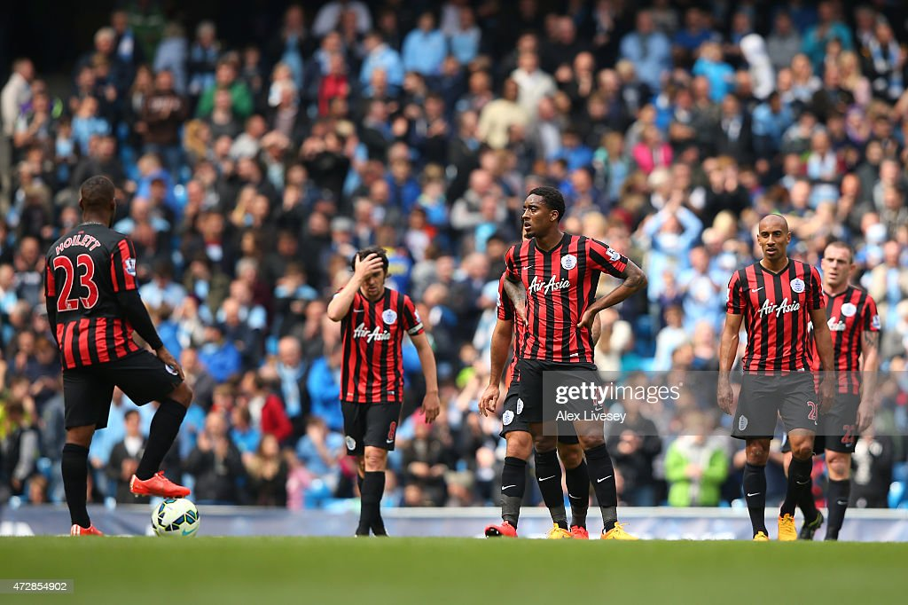 Dejected QPR players look on during the Barclays Premier League match between Manchester City and Queens Park Rangers at the Etihad Stadium on May 10, 2015 in Manchester, England.