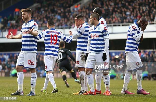 Dejected Queens Park Rangers players after Shaun Maloney of Wigan Athletic scores the equalising goal during the Barclays Premier League match...