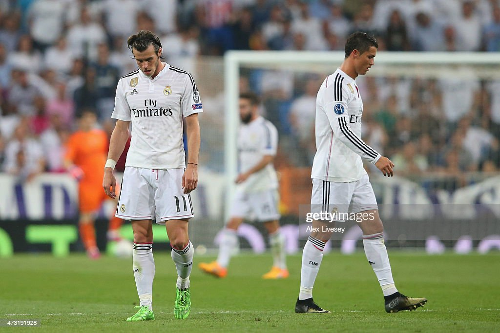 Dejected Real Madrid teammates Gareth Bale and Cristiano Ronaldo walk off the pitch following their team's exit from the competition during the UEFA Champions League Semi Final, second leg match between Real Madrid and Juventus at Estadio Santiago Bernabeu on May 13, 2015 in Madrid, Spain.