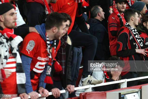 A dejected Rennes fan holds his head in his hands during the UEFA Europa League Round of 16 Second Leg match between Arsenal and Stade Rennais at...