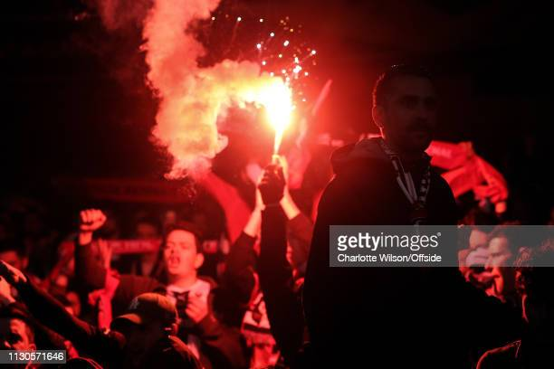 A dejected Rennes fan is silhouetted against a red flare during the UEFA Europa League Round of 16 Second Leg match between Arsenal and Stade Rennais...