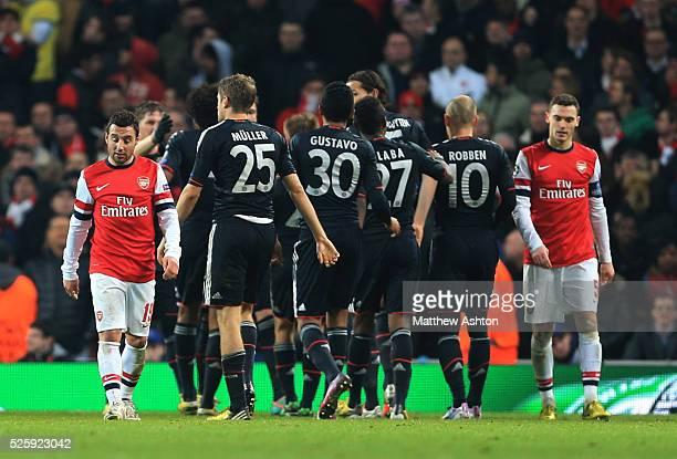 A dejected Santi Cazorla and Thomas Vermaelen of Arsenal walk past as Bayern Munich celebrate scoring a goal to make it 13