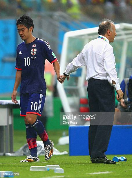 Dejected Shinji Kagawa of Japan walks off the field shaking hands with Alberto Zaccheroni after being defeated by the Ivory Coast 2-1 during the 2014...