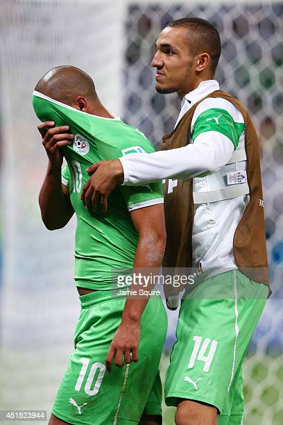 A dejected Sofiane Feghouli and Nabil Bentaleb of Algeria look on after being defeated by Germany 21 during the 2014 FIFA World Cup Brazil Round of...