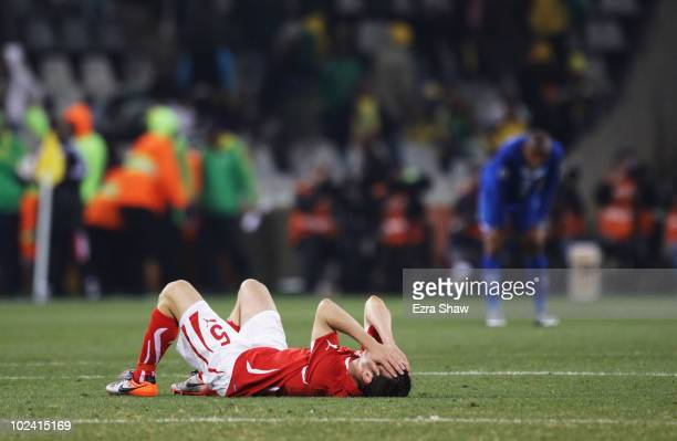 Dejected Steve von Bergen of Switzerland lies on the pitch after a goalless draw and elimination from the tournament during the 2010 FIFA World Cup...