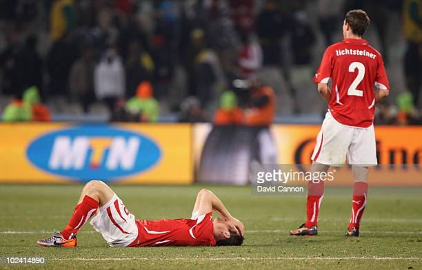 Dejected Steve von Bergen of Switzerland lies on the pitch while Stephan Lichtsteiner looks on after a goalless draw and elimination from the...
