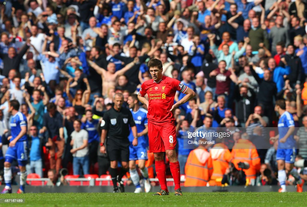 A dejected Steven Gerrard of Liverpool looks on as the Chelsea fans celebrate after Willian of Chelsea scored their second goal during the Barclays Premier League match between Liverpool and Chelsea at Anfield on April 27, 2014 in Liverpool, England.