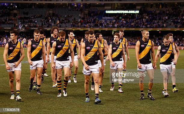 Dejected Tigers players leave the ground after the round 15 AFL match between the North Melbourne Kangaroos and the Richmond Tigers at Etihad Stadium...