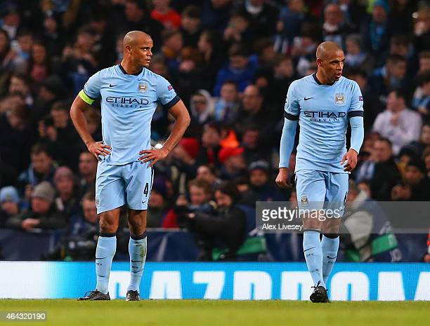 A dejected Vincent Kompany and Fernando of Manchester City look on during the UEFA Champions League Round of 16 match between Manchester City and...