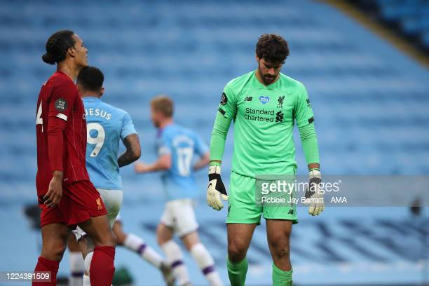 A dejected Virgil Van Dijk and Alisson Becker of Liverpool after Manchester City scored to make it 30 during the Premier League match between...