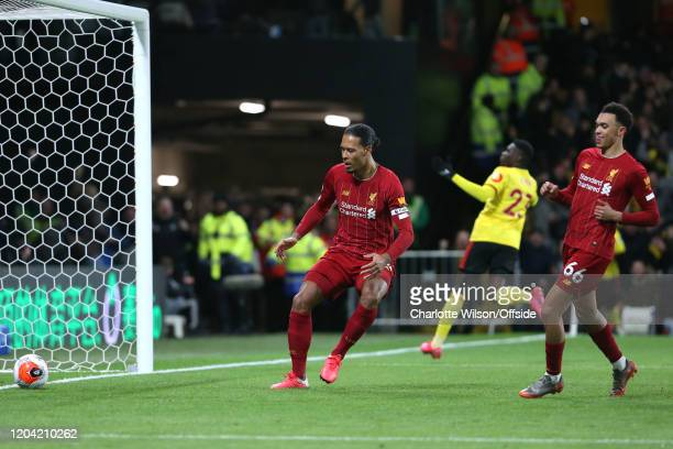 A dejected Virgil van Dijk of Liverpool collects the ball from the empty net after the 2nd Watford goal as a sheepish Trent AlexanderArnold of...