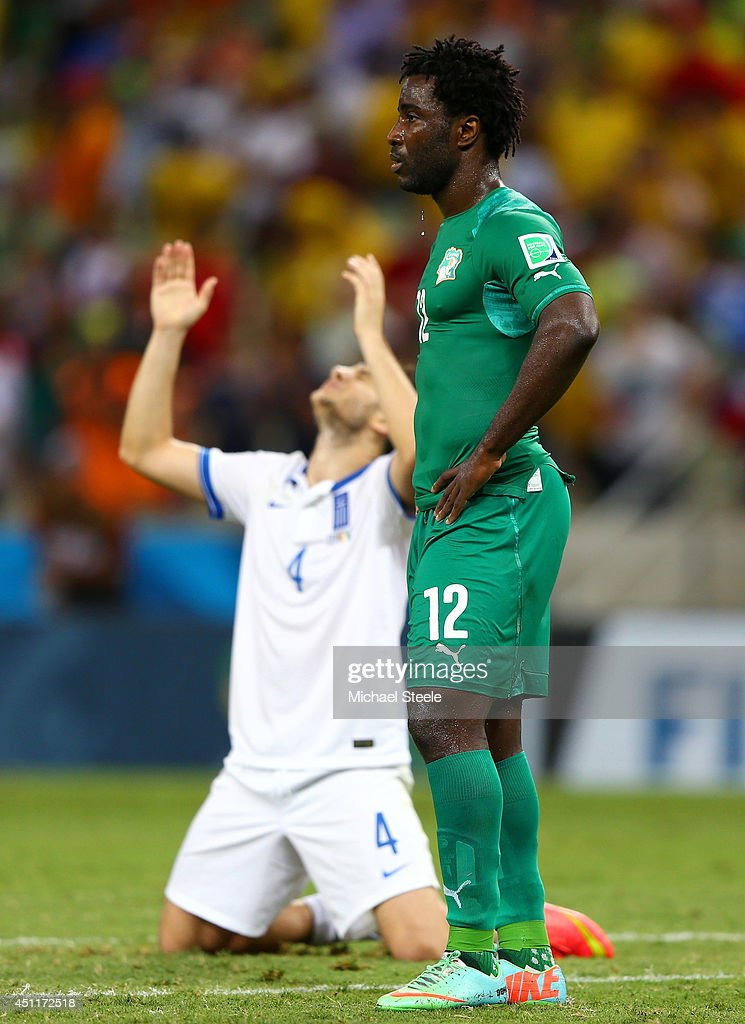 A dejected Wilfried Bony of the Ivory Coast looks on as Konstantinos Manolas of Greece celebrates during the 2014 FIFA World Cup Brazil Group C match between Greece and the Ivory Coast at Castelao on June 24, 2014 in Fortaleza, Brazil.