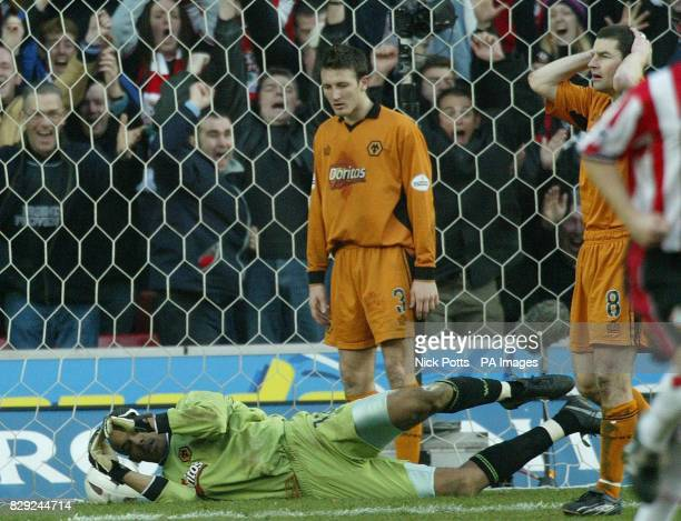 Dejected Wolverhampton Wanderers defenders Lee Naylor and Denis Irwin both look at goalkeeper Matt Murray after he let ball go through his hands for...