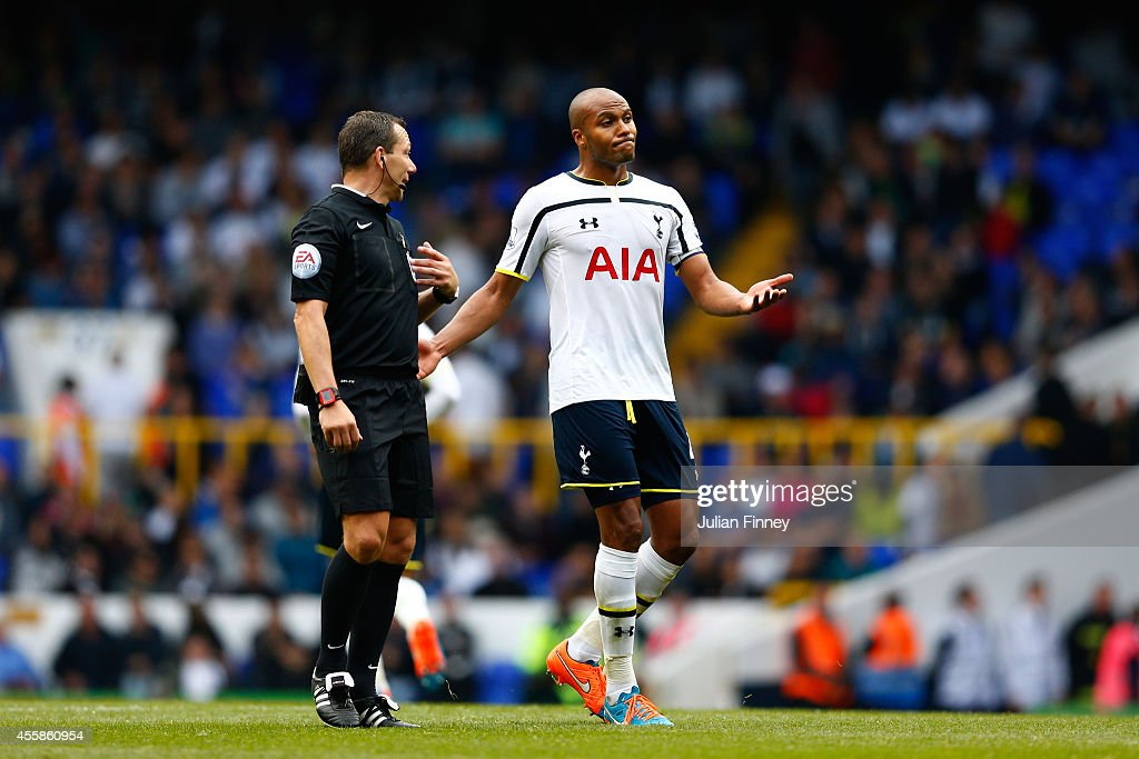 A dejected Younes Kaboul of Spurs speaks with Referee Kevin Friend following his team's 1-0 defeat during the Barclays Premier League match between Tottenham Hotspur and West Bromwich Albion at White Hart Lane on September 21, 2014 in London, England.