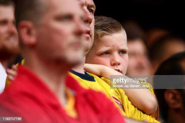 A dejected young fan of Arsenal looks on during the Premier League match between Liverpool FC and Arsenal FC at Anfield on August 24 2019 in...