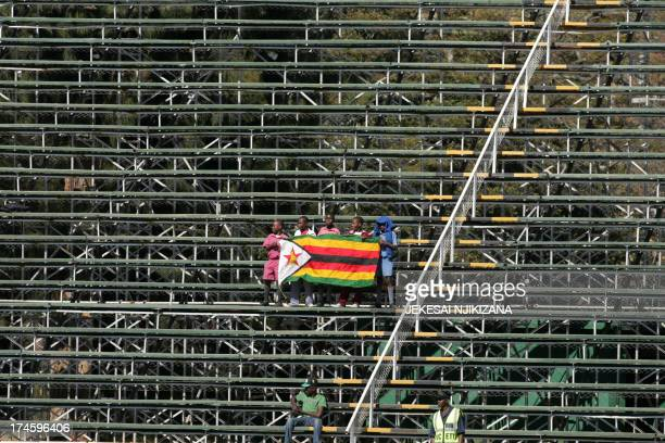 Dejected Zimbabwe fans hold their flag as their team struggles to make runs during the 3rd match of the 5 cricket ODI series between Zimbabwe and...