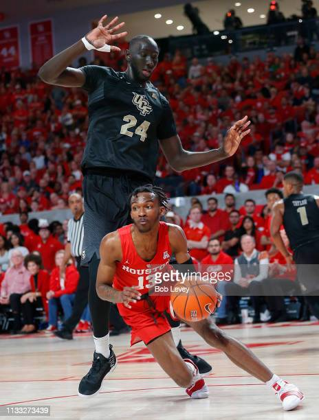 Dejon Jarreau of the Houston Cougars drives baseline past Tacko Fall of the UCF Knights during the second half at Fertitta Center on March 02 2019 in...