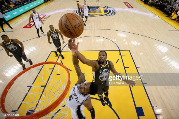 Dejounte Murray of the San Antonio Spurs and Kevin Durant of the Golden State Warriors go for a rebound during Game 2 of Round 1 of the 2018 NBA...