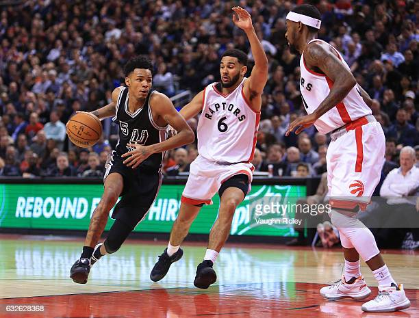 Dejounte Murray of the San Antonio Spurs dribbles the ball as Cory Joseph of the Toronto Raptors defends during the second half of an NBA game at Air...
