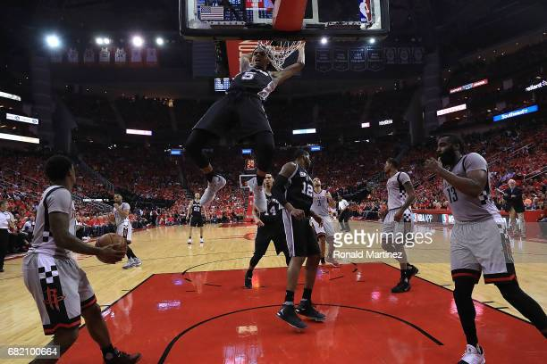 Dejounte Murray of the San Antonio Spurs dunks against James Harden and Lou Williams of the Houston Rockets during Game Six of the NBA Western...